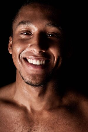 Young sweaty smiling male on black background
