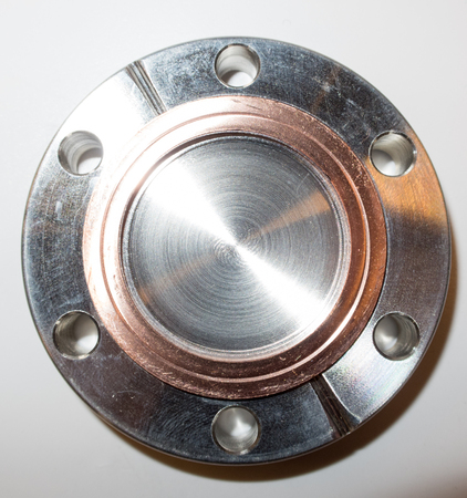 flange: Ultra high vacuum flange with used copper seal typically used in a physics science lab.