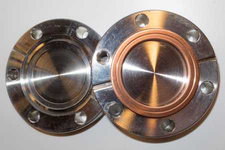 stainless steal: Two ultra high vacuum flanges, one with a used copper seal, typically used in an physics science lab. Stock Photo