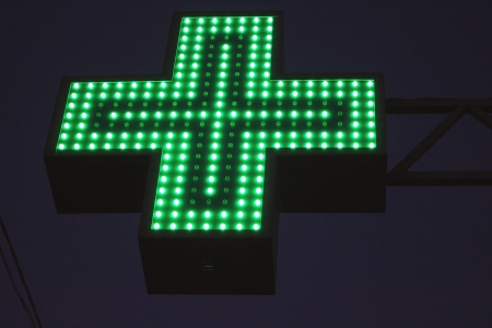 Neon green cross sign by night