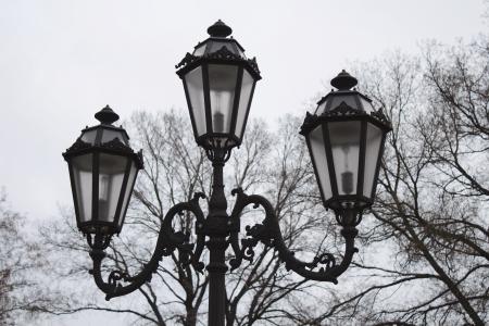 Vintage triple street lamp at cloudy day 免版税图像