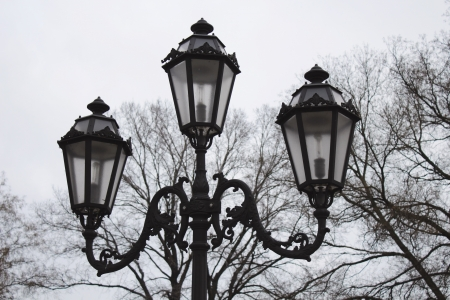 Vintage triple street lamp at cloudy day Standard-Bild
