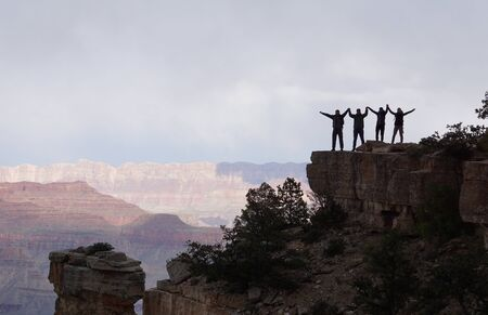 Four people standing at a cliff