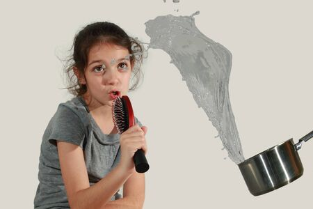 badly: Young girl singing badly and receiving a saucepan of water