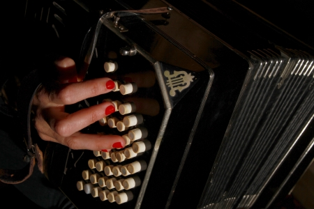 Woman s hand on a bandoneon keyboard