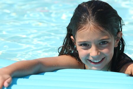 Young girl in a swimming pool on an inflatable sun bed photo