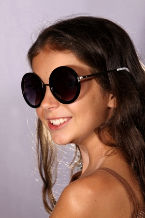 suntanned: Pretty young girl posing with a pair of sunglasses