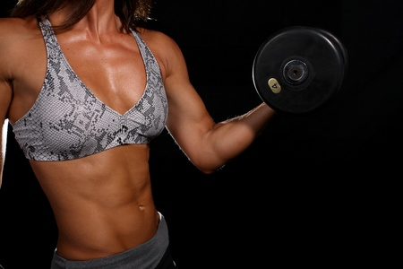 Attractive girl with dumbbell in the gym