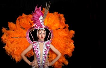 Cabaret dancer in costume posing on a black background Standard-Bild