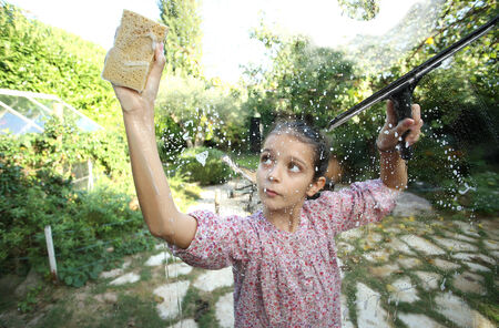 sudsy: Young girl cleaning windows Stock Photo