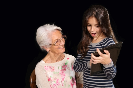 Grand mother and grandchild posing on a black with a pc tablet photo