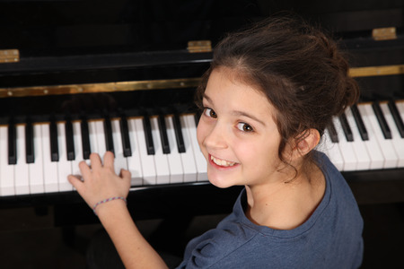 upright piano: Young girl playing piano Stock Photo