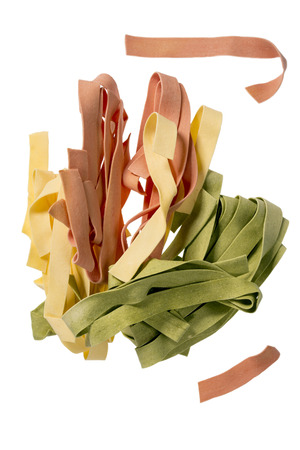 Different colored pasta on a white background
