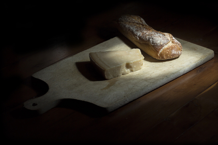 French bread and Parmesan cheese on a cheese board. Dark background Reklamní fotografie