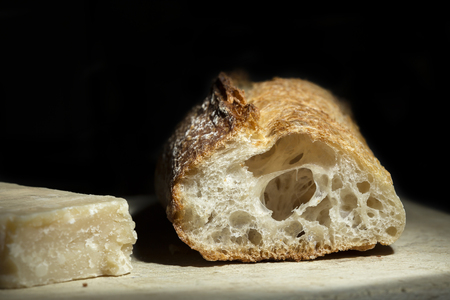 French bread and Parmesan cheese on a cheese board. Dark background Standard-Bild