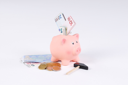 pink Piggy bank with Hammer Euro bills and Euro coins photo