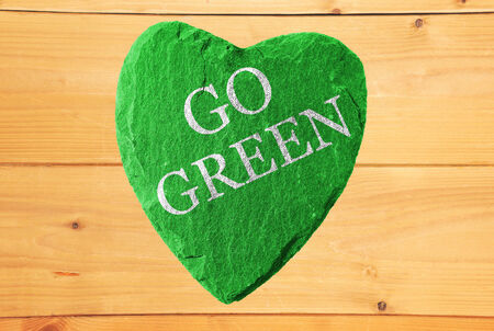 ecologist: green heart with go green writing and wooden background Stock Photo