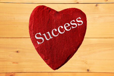 and is favorable: red heart with success and wooden background