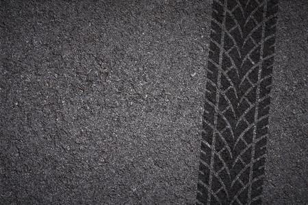 アスファルトのテクスチャ上のタイヤのトラック