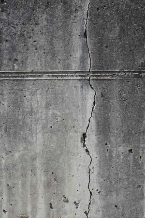 fissure: Dirty weathered concrete wall with long fissure