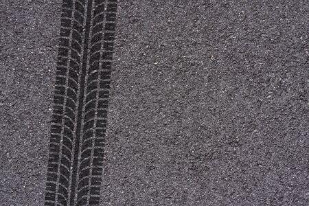 タイヤがアスファルトの背景にマークを踏む
