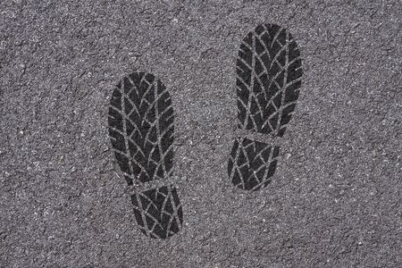 skidmark: Footprint of shoes with tire tread pattern on asphalt background