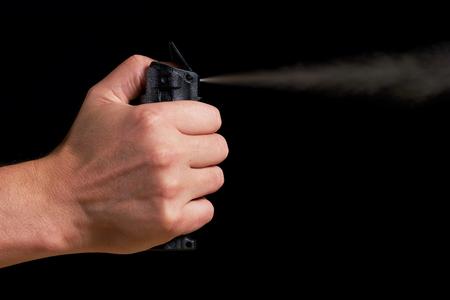 man gericht en spuiten pepperspray met zichtbare mist op zwarte achtergrond