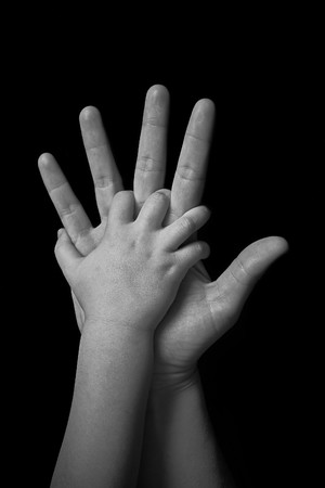 mother and child holding hands on black background