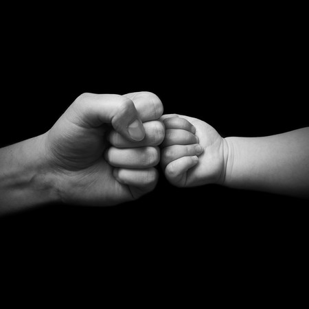 father and child touching fist on black background