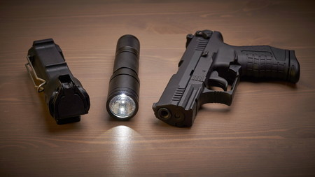 self defense gear - pistol, pepper and tactical flashlight on wooden surface Archivio Fotografico