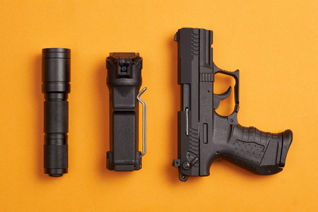 self defense gear - pistol, pepper and tactical flashlight on orange background