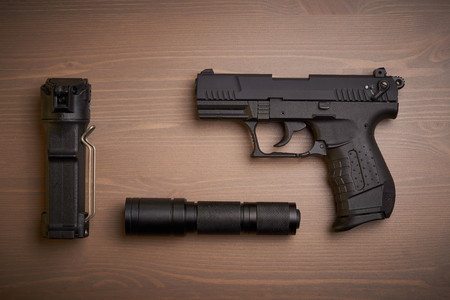 self defense gear - pistol, pepper and tactical flashlight on wooden surface Stockfoto