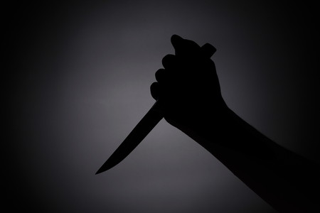 attacking with a knife. black silhouette in the dark