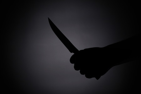Attacking with a knife. black silhouette in the dark 写真素材
