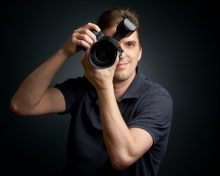 Male photographer taking a picture straight ahead of you 写真素材