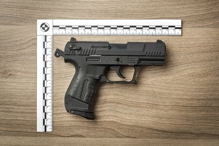 Crime Scene Investigation - handgun as a piece of evidence placed with forensic rulers for documentation