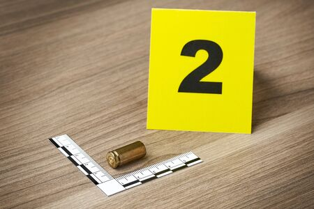 Crime Scene Investigation - bullet as a piece of evidence placed with forensic rulers and yellow markers for documentation