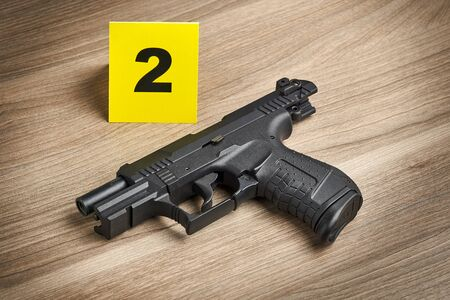 Crime Scene Investigation - handgun as a piece of evidence tagged by yellow marker