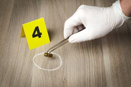 Enquête sur les lieux du crime - officier de police scientifique recueillant une balle comme élément de preuve