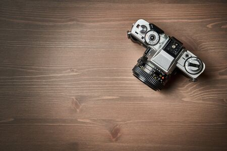 top view of a Classic analog 35 mm camera vintage on wooden table