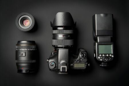 top view of modern digital camera equipment - DSLR with attached zoom lens and hood, lenses and external flashlight on black surface