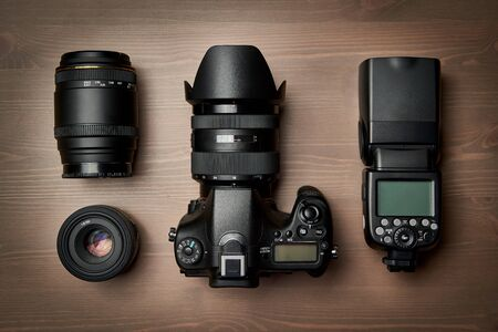 top view of modern digital camera equipment - DSLR with attached zoom lens and hood, lenses and external flashlight on wooden table 写真素材