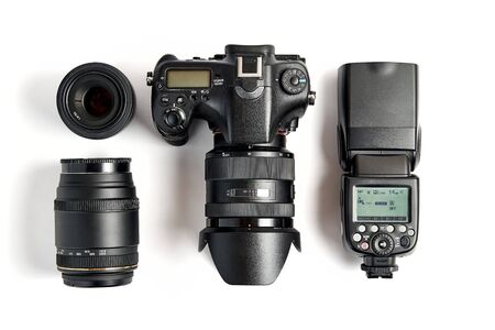 top view of modern digital camera equipment - DSLR with attached zoom lens and hood, lenses and external flashlight on white background 写真素材