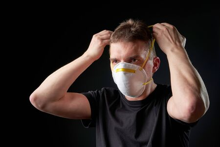 young man putting on a protective mask in dark atmosphere