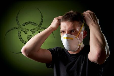 young man putting on a protective mask in dark atmosphere - black biohazard sign / emblem on green background