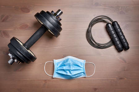 fitness gear dumbbell, jumping rope and protective mask on wooden surface
