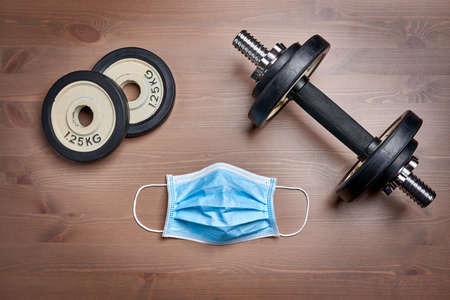 fitness gear dumbbell, weight plates and protective mask on wooden surface