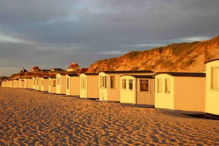 In Denmark, Scandinavia, Europe. Bath houses on the beach of Lokken, Northern Jutland, in evening light.