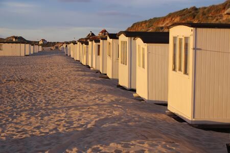 In Denmark, Scandinavia, Europe. Bath houses on the beach of Lokken in evening light.