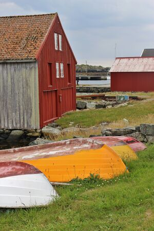 Typical wooden house on the isle of Utsira in Norway with colorful boats. Stock Photo